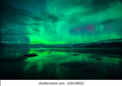 Northern lights (Aurora Borealis) and fast moving clouds reflected over water and icebergs  of glacial lagoon Jokulsarlon in Iceland.