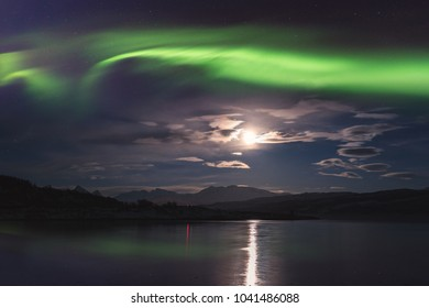Northern lights (aurora borealis) in Lofoten islands, Norway. Amazing night winter landscape with polar lights, starry sky with full moon and reflection in the water