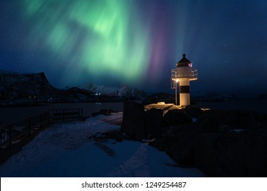 Northern lights, Aurora borealis in Lofoten islands, Norway. Amazing night winter landscape with polar lights and starry sky over the lighthouse in Kabelvag fishing village