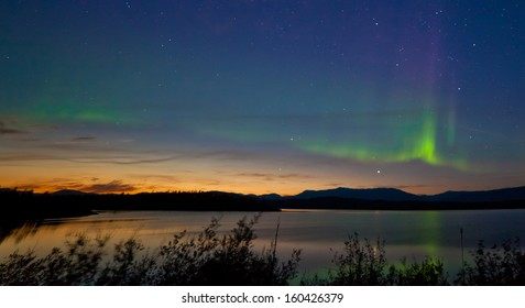 Northern lights  Aurora borealis  at midnight in summer over northern horizon of Lake Laberge  Yukon Territory  Canada  at early dawn