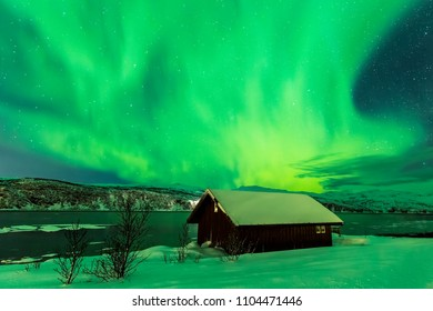 Northern lights Aurora Borealis in the night above a typically artic style build house in Troms county, Norway. The sky is a bit clouded the landscape is lit green by the northern lights.