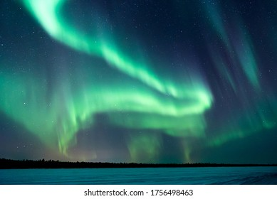 Northern lights, aurora borealis in the night sky over frozen lake in Lapland, Finland
