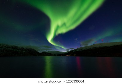 Northern lights ( aurora borealis ) over lake in Norway and wind turbines in the background