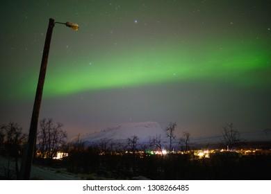 Northern lights, aurora borealis over Mountains Saana in Kilpisjärvi, Finland, with stars in sky