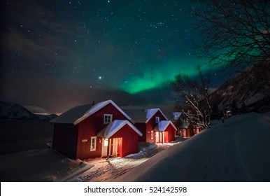 Northern lights (Aurora Borealis) over the red snowed-in cottages in Lapland village