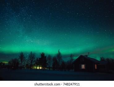 Northern lights (Aurora Borealis) over snowed-in cottage in Lapland village. Finland