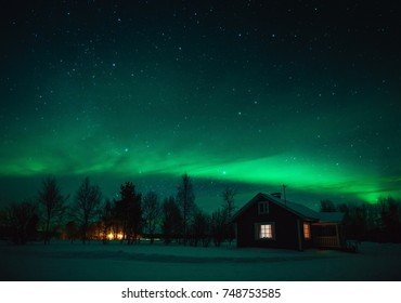 Northern lights (Aurora Borealis) over snowed-in cottage in Lapland village. Finland