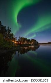 Northern Lights (Aurora Borealis) reflected over lake in Kiruna, Sweden.