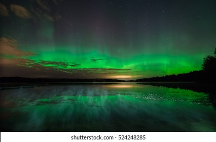 Northern lights (Aurora borealis) reflected over the lake with mist rising over water in the end of summer. Stockholm, Sweden.