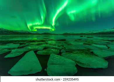 Northern lights (Aurora borealis) reflection across a lake in Iceland.Contains Noise.