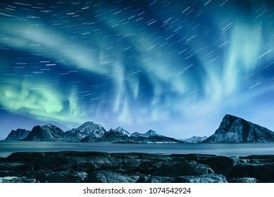 Northern Lights, Aurora Borealis shining green in night starry sky with star tracks at winter Lofoten Islands, Norway