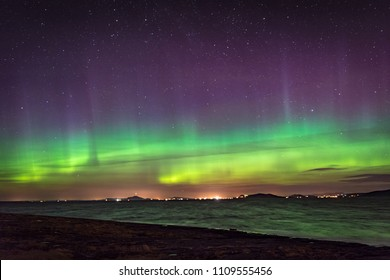 Northern lights aurora at seaside color and beams