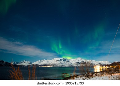 Northern lights, Aurora seen in polar region landscape and fjord mountain over the night sky in Norway