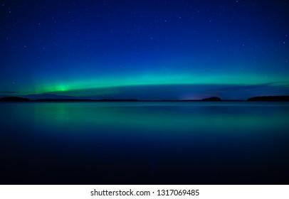 Northern lights background in Farnebofjarden national park in Sweden.