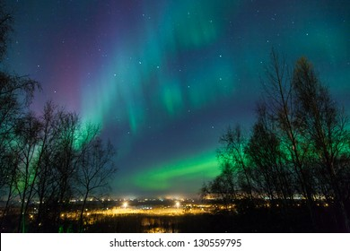Northern lights and Big Dipper shine brightly over a city