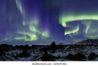 Northern Lights bursting above an Arctic rocky landscape