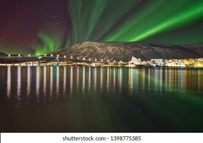 The Northern Lights in the city of Tromso, Norway. The colours of the lights and the reflection of these in the fjord enhances the magical beauty of nature.