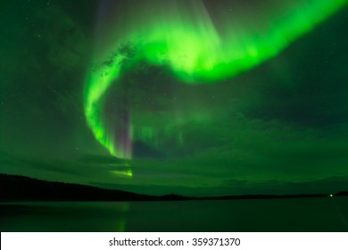 Northern Lights in Cloudy Sky - Bright northern lights shining through cloudy night sky over a lake.