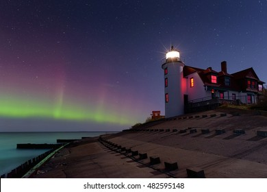 Northern Lights dancing in the night sky at Point Betsie Lighthouse, lake Michigan