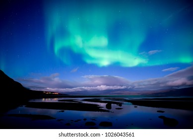 Northern lights dancing over calm lake in Abisko national park in Sweden
