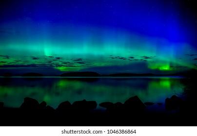 Northern lights dancing over calm lake. Farnebofjarden national park in Sweden