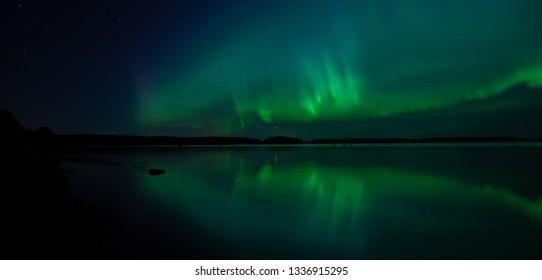 Northern lights dancing over calm lake in Farnebofjarden national park in Sweden.