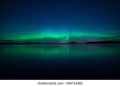 Northern lights dancing over calm lake in Sweden (Aurora borealis) Farnebofjarden national park.