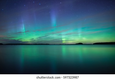 Northern lights dancing over calm lake in sweden (Aurora borealis)