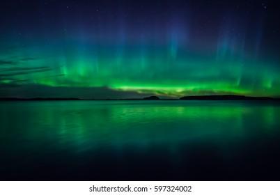 Northern lights dancing over calm lake in sweden (Aurora borealis)
