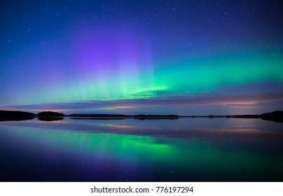 Northern lights dancing over calm lake. Farnebofjarden national park in Sweden.