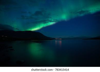Northern lights dancing over calm lake in Abisko