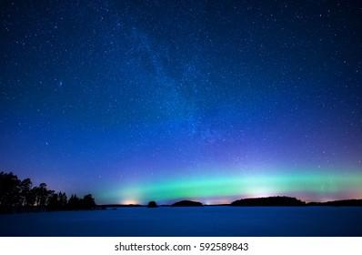 Northern lights dancing over frozen lake in Sweden (Aurora borealis)