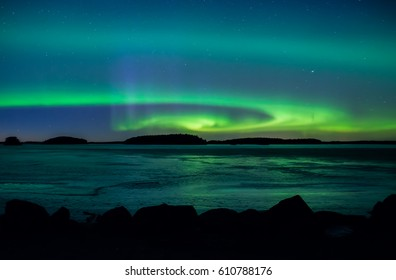 Northern lights dancing over frozen lake in spring