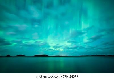 Northern lights dancing over frozen lake in Farnebofjarden national park in Sweden