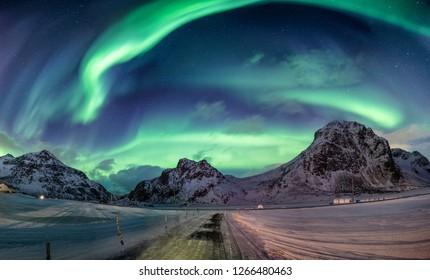 Northern lights explosion on snowy mountain range near coastline at Lofoten islands, Norway