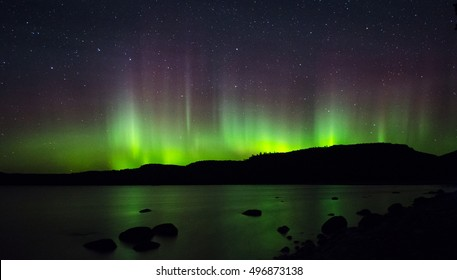 Northern Lights form a curtain of color over the Ontario hills.