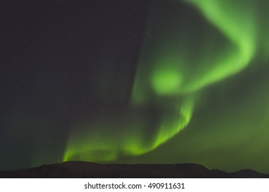 Northern lights in Iceland, Aurora borealis near Reykjavik in autumn. Green starry night sky.