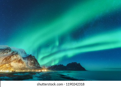 Northern lights in Lofoten islands, Norway. Green Aurora borealis. Starry sky with polar lights. Night winter landscape with aurora, sea with sky reflection, rocks, beach and snowy mountains. Nature
