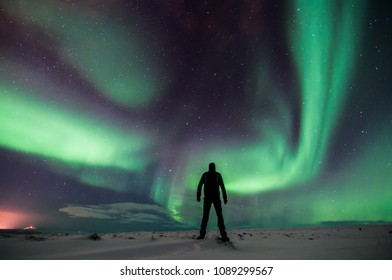 Northern lights with man in north Iceland, winter