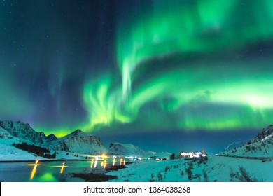 Northern lights at night against the backdrop of beautiful mountains by the ocean at a time of winter in Norway in the Lofoten Islands