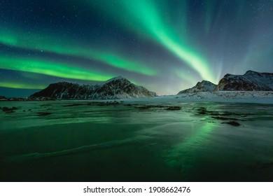 Northern Lights on the night sky. Aurora Borealis over Skagsanden beach on Lofoten Islands. Northern Norway. Wintertime starry sky.