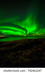 Northern lights over calm waters seen from Reykjanes peninsula in Iceland.