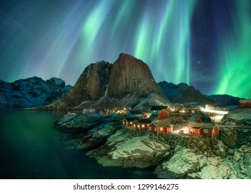 Northern lights over fishing village with mountain range on coastline at Hamnoy, Lofoten