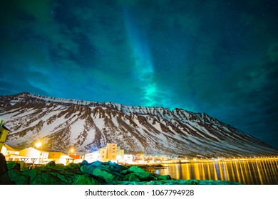 northern lights over the mountains and a cloudy sky