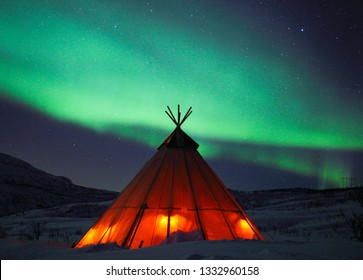 Northern lights over a Sami lavvu.