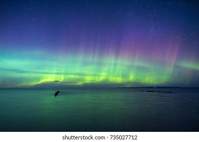 The northern lights put on a display of green and pink pillars in the night sky over Lake Superior.