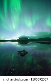 Northern lights reflected on a lake in Kilpisjärvi, Lapland, Finland. Mt.Saana in the background.