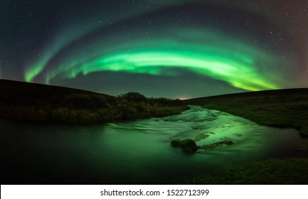 Northern lights with reflection in river, North Iceland