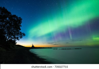The northern lights shine just after sunset along the Lake Superior coast. Orange color can be seen from twilight along with some blue, purple, and green bands from the aurora.