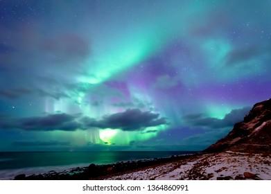 Northern lights shining at Unstad beach in Lofoten, Norway